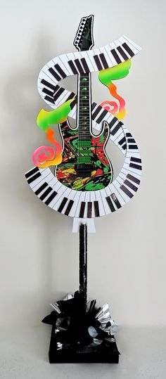Want a music centerpiece that says WOW! Here's one that combines a colorful foamcore guitar, piano keyboard with 3D glittery keys and big funky musical notes all in one with a pole and decorative base. #guitarcenterpiece #pianokeyboard #partydecor