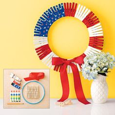 a DIY, independence day patriotic wreath made from wood clothespins painted in red, white, and blue, and attached in a radiating circle with a red bow, hung on a yellow wall next to a vase filled with flowers, and an inset image of the materials used