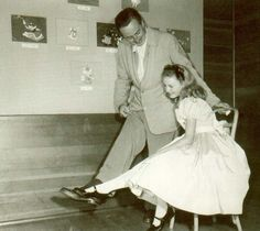 Walt Disney and Kathryn Beaumont (the actress who voiced Alice) comparing shoe sizes