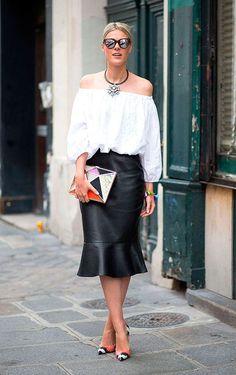 Foto de street style com blusa de ombros à mostra branca e saia midi de couro