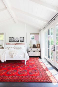Bright and airy bedroom with a large red area rug, and a white canopy bed