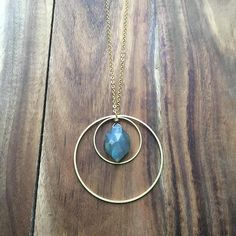 """Faceted blue flash labradorite hexagon with brass ring accents. Brass chain with lobster claw clasp. Clasp is accented with faceted labradorite. Chain measures approximately 24 1/2"""" in length and pendant measures approximately 1 3/4"""" in length. Great necklace for layering."""