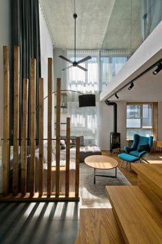 salon moderne aménagé avec une cloison bois, un canapé gris et un fauteuil bleu