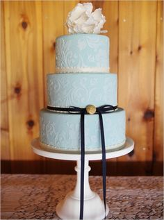 Love this cake; the light blue, lace detail, black ribbon and modern big bloom topper :))