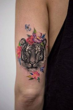 Beautiful arm tattoo depicting a tiger's head which is decorated with some nice…