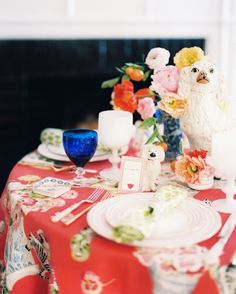 A round table set with vases of flowers and Staffordshire-dog figurines.