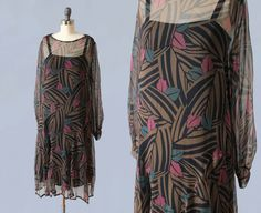 Incredible 1920s dress with very special rare super Art Deco jungle leaves print!! Light as air sheer silk chiffon. Ruched shoulders with snaps on left shoulder. Long sleeves with snaps at wrists. Loose forgiving shape and flattering arched seaming at hips. Flowy skirt. Simple, elegant and cool.  Measurements: *no closures, slips over the head *meant to fit loosely. Recommended for a size XS-M -Bust: 41 -Dropped waist: 39 (19 from shoulder) -Length: 41.5  Condition: Great. Ruching at…