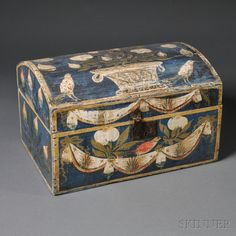 Paint-decorated Dome-top Box, America, early 19th century, the blue-painted box with hinged lid, wire handle, and iron latch, with polychrome painted decoration: the top with a basket of flowers flanked by birds, the front with drapery festoons, bowknots, a bird, and fruit, and the two sides with budding branches, (imperfections), ht. 11 1/2, wd. 19, dp. 13 1/4 in.