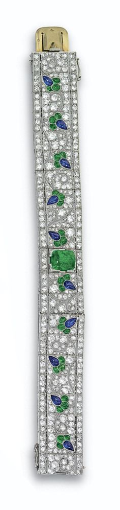 EMERALD, SAPPHIRE AND DIAMOND BRACELET, FRENCH, CIRCA 1925. The articulated band decorated in a meandering floral motif set with buff-top calibré-cut emeralds and sapphires, the center set with a cushion-shaped cabochon emerald weighing approximately 3.75 carats, within a ground of pavé-set old European-cut and single-cut diamonds weighing approximately 13.50 carats, mounted in platinum, length 71⁄4 inches, maker's mark JD and French assay mark.