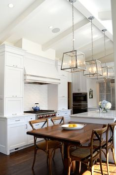 Gorgeous kitchen boasts vaulted ceiling accented with wood beams over seeded glass lanterns ...