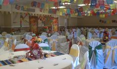 Colorful sarape runners, different color bows on chairs, hanging banners (papel picado).