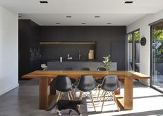 M House is a minimalist house located in Melbourne, Australia, designed by DKO. The kitchen space features blacked out custom cabinetry with a black kitchen island that allows for seating and serving.
