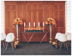 Wedding ceremony decor at Le Méridien Tampa in Tampa, FL with white molded plastic mid-century modern chairs and florals  in a palette of orange and coral by Botanica International Design & Decor Studio. Image by Papered Heart Photography.