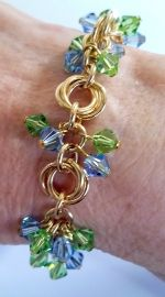 "Gold Filled Chain Maille bracelet. Swarovski ""flowers"" in peridot and sapphire."