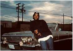 Ice Cube in his O. Young, standing next to his chevy, enjoying life.