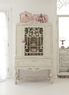 Pink bird cage and crown actually sets off the shabby white cabinet. Love the scroll work on the front.