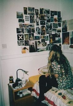 Bedroom. Simple unfinished looking endside table with random knicknacks a polaroid collection the wall.