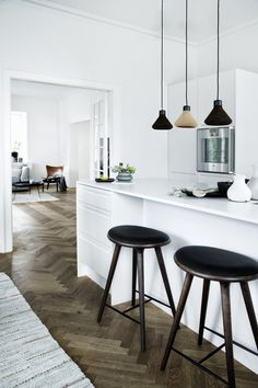 Interior Design. Kitchen Design. Minimalist. White. Wooden Pendant Lights. Herringbone Floor Boards.