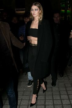 After her Atelier Versace catwalk appearance, Gigi Hadid was spotted outside the show wearing high-waist trousers, a bandeau top and tailored coat.   - HarpersBAZAAR.co.uk