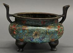 Cloisonne enameled tripod censer, featuring stylized lotus issuing from scrolling tendrils on a turquoise ground, flanked by upturned handles and short supports, the underside with a Ming Xuande mark.