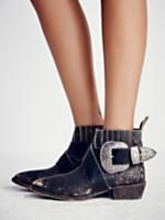 Understated Biker Boot | Leather Chelsea style ankle boots featuring a western-inspired wraparound belt with an etched buckle detail. Sleek pointed toe design. Distressing throughout for a cool, lived-in look. Back pull tab for an easy on-off. Small chunky heel creates a comfortable step. Lift your shoe for a cheeky
