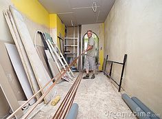 A contractor preparing materials (pipes and boards), putting them on the floor. Home interior being renovated, mess all around.  <a href='http://www.dreamstime.com/interiors-rcollection5192-resi208938' STYLE='font-size:13px; text-decoration: blink; color:#FF0000'><b>HOME BUILDING & RENOVATION »</b></a>