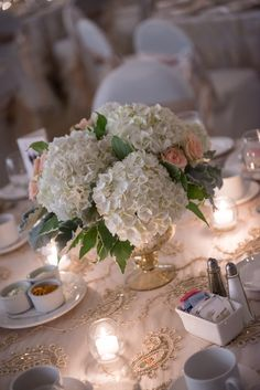 Hydrangea, spray roses, variegated greens and dusty miller! All come together to make this stunning centerpiece!