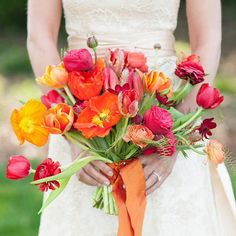 Hand Tied Bridal Bouquet Showcasing: Red Ranunculus, Red Tulips, Orange Tulips, Sangria Orchids, Red-Orange Poppies, Orange Poppies, Greenery