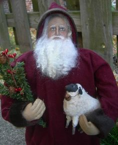 PRIMITIVE FOLK ART CHRISTMAS OLD WORLD SANTA DOLL WITH SHEEP BY JANE.. Santa is weighted and 16 inches tall.  He comes with decorative evergreens and two sheep that stand 3 1/2 and 4 1/2 inches tall.