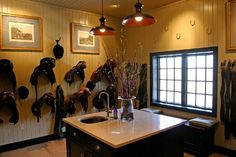 Organized tack room with marble countertop and sink for cleaning tack.
