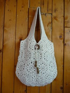 Hand crochet bag with an 100% cotton . No lining , big coconut button, is decorated with wood beads. Measurements : H: 34 cm x W 33 cm ( H: 13,6 inches x W: 13 inches ) Handles: up to 43 cm ( 17 inches)