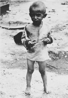 Portrait of an emaciated, partially clothed child in the Jasenovac concentration camp.