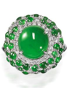 A jadeite and diamond ring The highly translucent jadeite cabochon of bright emerald green colour, measuring approximately 9.9 x 8.9 x 4.6mm, within a brilliant-cut diamond surround, accented by similarly cut diamonds and smaller jadeite cabochons