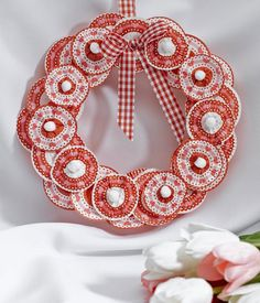 """Be My Valentine Wreath ~1-2 pkg red cupcake wrappers, 9″ sheet thick craft foam, Roll red crepe paper, 10 small white pom-poms, 1 yd red check ribbon, Hot glue and gun, 10-12 round toothpicks, scissors, straight pins  ~Wrap crepe paper around wreath,secure ends w/pin~Wrap 18"""" ribbon around top of wreath for hanger. Pin or glue in place.  ~Flatten cupcake wrappers around wreath~Cut 10, 1/2"""" sq pieces from craft foam...."""