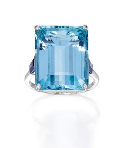PLATINUM, AQUAMARINE AND SAPPHIRE RING The emerald-cut aquamarine weighing approximately 24.00 carats, flanked by two tapered baguette sapphires