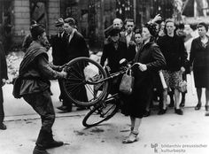 A German woman arguing with a Red army soldier over her bicycle. Berlin, Spring-Summer 1945