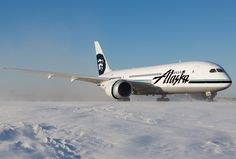 Alaska Airlines Boeing 787-8 Dreamliner on a runway covered with snow.