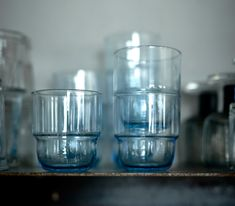 A close-up of a tumblers with a light blue tint, shown stacked.