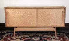 New credenza design featuring White Oak and Ash cradle, Red Oak handles and birch veneered plywood panels. Bookmatched sliding doors and adjustable shelves in Birch ply.