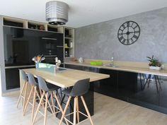 Grande cuisine équipée avec des façades noires brillantes associées à un bois clair pour plus de luminosité. Un îlot central idéal pour rassembler toute la famille autour de bons petits plats ! #cuisine #cuisinenoireetbois #luminosité #îlot #moderne #design