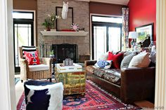 Stenciled Drapes! Love the red-orange paint with the black framed doors...the red & blue rug with the blue & white drapes.  AND the animal print chair!