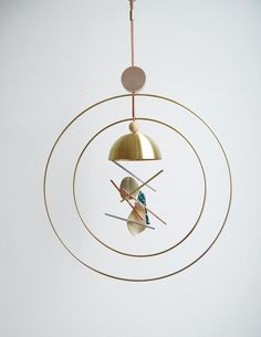 LGstudio. Two brass Aura Rings surround a polished brass bowl, metal tubes and ceramic chimes handmade by Seattle artist Nicholas Nyland.