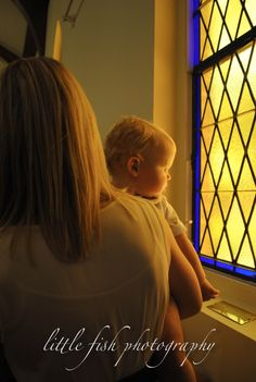 Baptismal photo: baby looking out of a church stained glass window