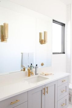 A light gray washstand, finished with antique brass pulls and white quartz countertop fitted with a sink paired with a brushed gold faucet, is positioned beneath a frameless vanity mirror lit by two mirror mounted brass industrial faucets.