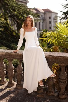 This minimalist and modest wedding dress with sleeves, a fitted bodice, and square neckline flows into a sweeping skirt. Made from high-quality and super soft matte crepe, you'll feel comfortable all day long in this number from Mila Bridal! #weddingdress #classicwedding #modestwedding #simpleweddingdress