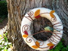 Yarn wrapped wreath with felt leaves and bird.