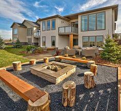 foyer extérieur en pierre de forme carré avec bancs en bois et troncs