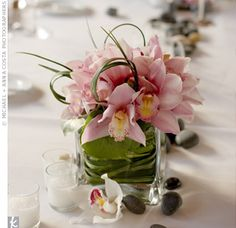 The Centerpieces Votive candles, beach stones and tiny, square glass vases filled with pink orchids, looped lily bear, and fern curls lined the tables.
