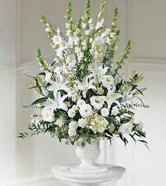 White lilies, white gladiolus and white lisianthus are accented with stock…