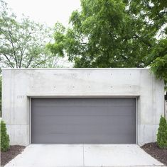 """The darker gray garage door offers a chromatic and textural contrast to the concrete shell. Tagged: Garage and Detached Garage Room Type. Search """"Garage"""" from Modern Urban Retreat in South Minneapolis. Browse inspirational photos of modern garages. Grey Garage Doors, Sliding Garage Doors, Garage Door Styles, Garage Exterior, Garage Door Design, Exterior Cladding, Minneapolis, Concrete Garages, Garage Door Makeover"""